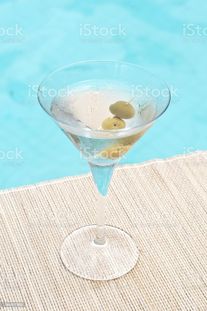 Classic dry martini cocktail near waterpool on the mat stock photo