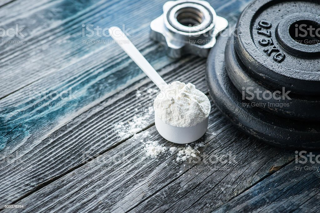 Classic dumbbell with protein powder on rustic wooden table stock photo
