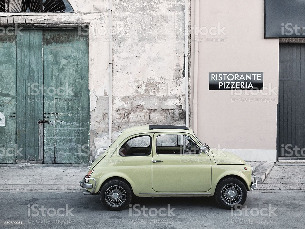Classic Fiat 500 in Sicily, Italy, near a pizzeria stock photo