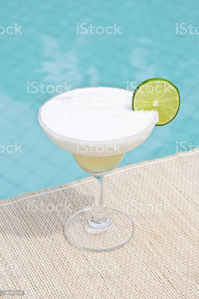 Classic Frozen Margarita cocktail near waterpool on the mat stock photo