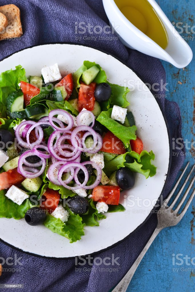 Classic Greek salad with sauce on a blue old background. stock photo