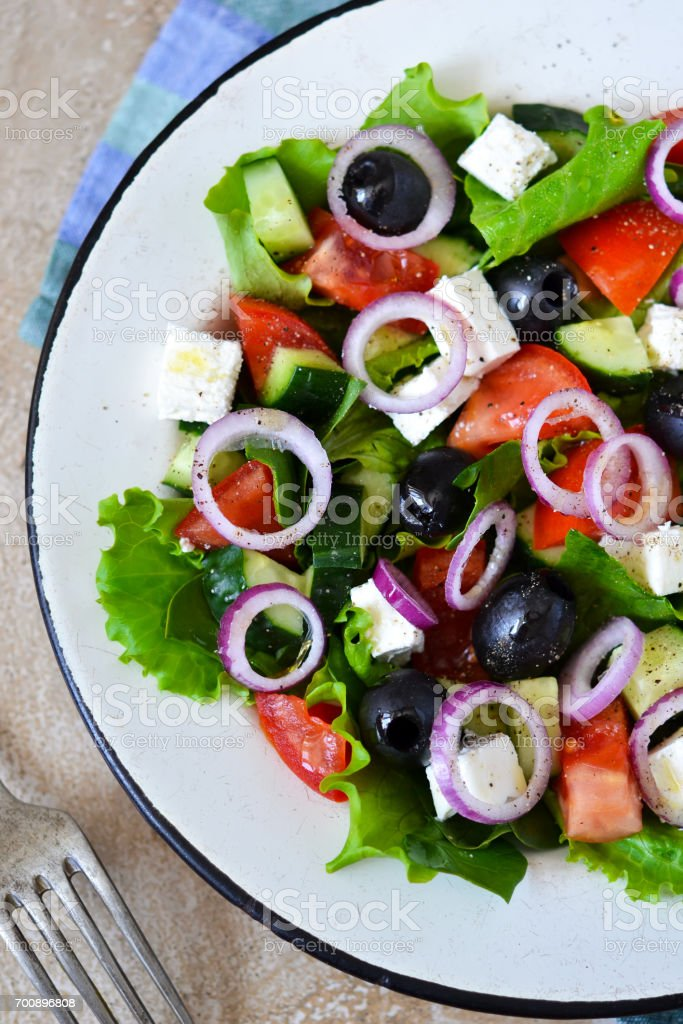 Classic Greek salad with sauce on a concrete background. Greek cuisine. stock photo