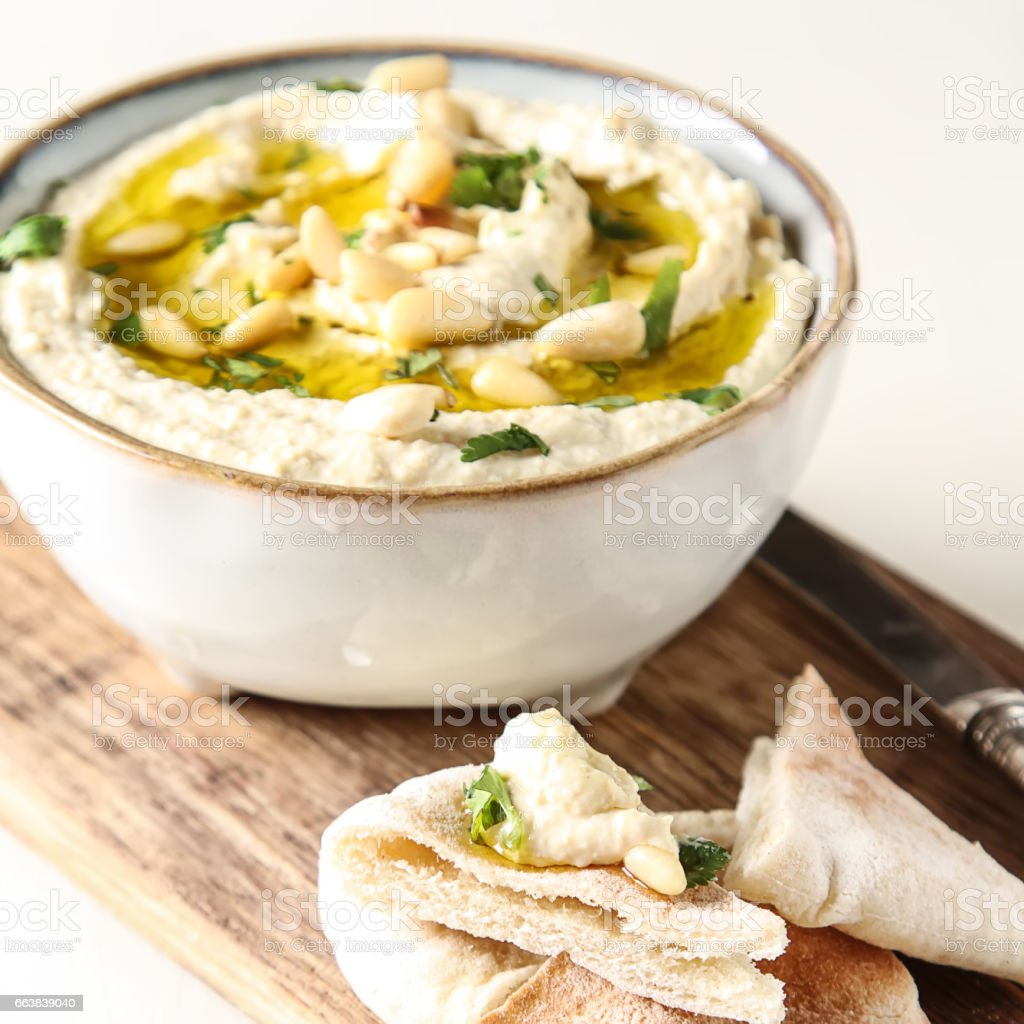 Classic hummus with herbs, olive oil in a vintage ceramic bowl and pita bread. Traditional Middle Eastern cuisine. Light white background. stock photo