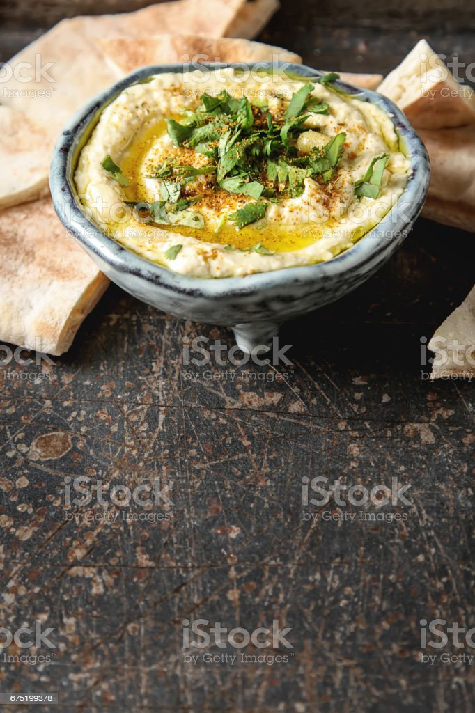 Classic hummus with herbs, olive oil in a vintage ceramic bowl and pita bread. Traditional Middle Eastern cuisine. Dark background. stock photo