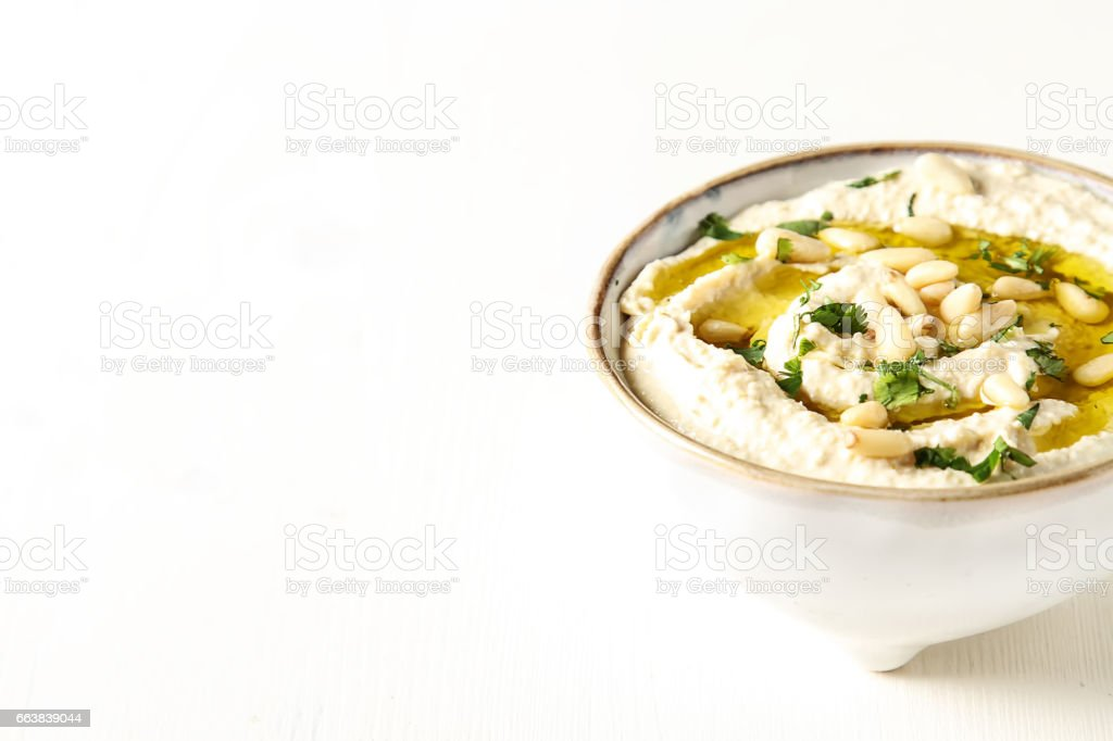 Classic hummus with herbs, olive oil in a vintage ceramic bowl. Traditional Middle Eastern cuisine. Light white background. stock photo
