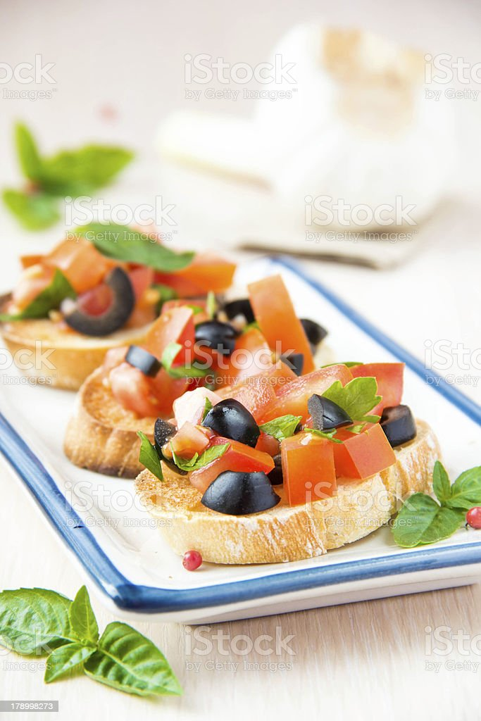 Classic Italian snack bruschetta with tomato, basil and olives royalty-free stock photo