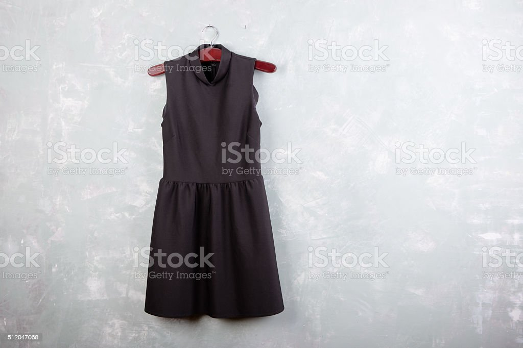Classic little black ladies dress on the wall stock photo