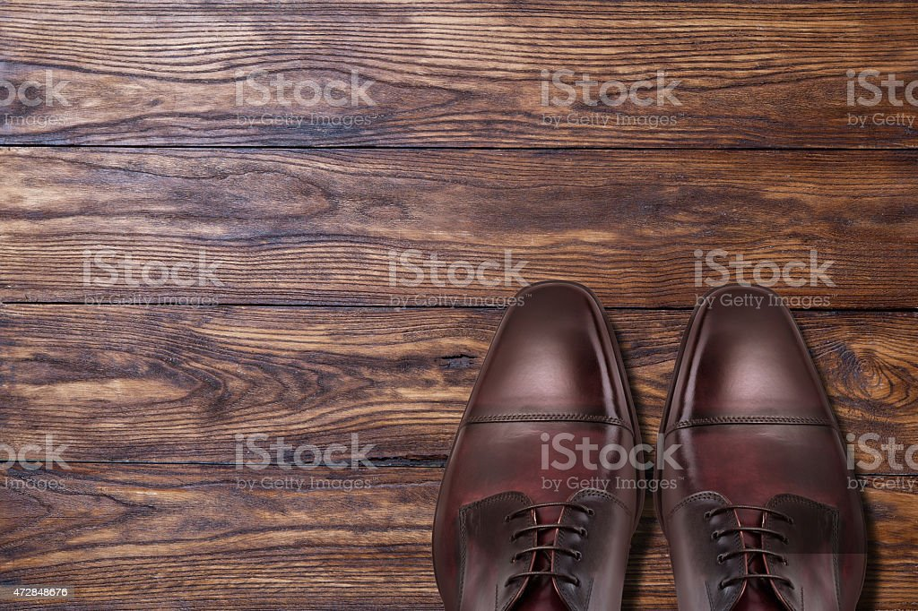 Classic male brown leather shoes on wood stock photo