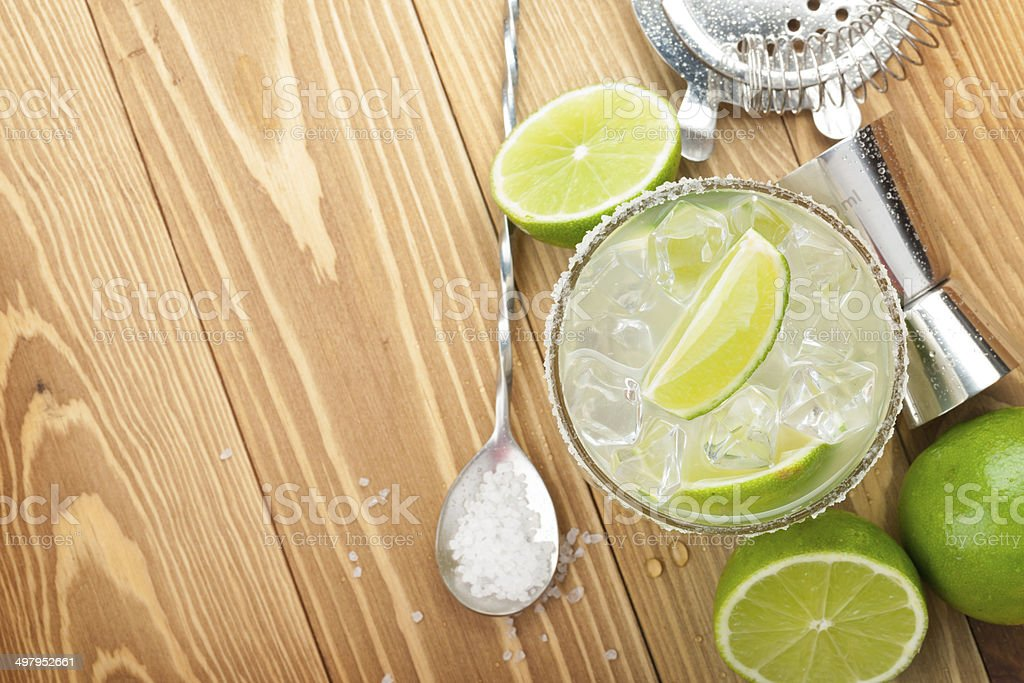 Classic margarita cocktail with salty rim on wooden table stock photo