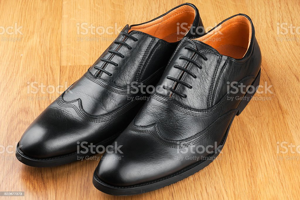 Classic men's shoes stand on the wooden floor stock photo