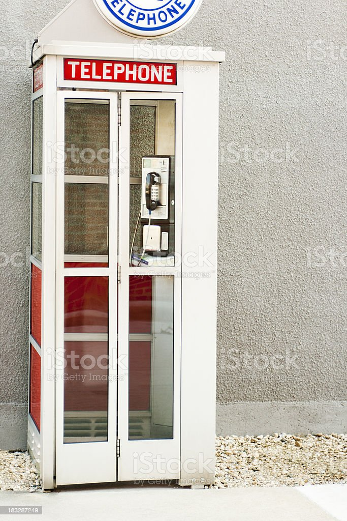 Classic Old-Fashioned American Phone Booth by Building Wall stock photo