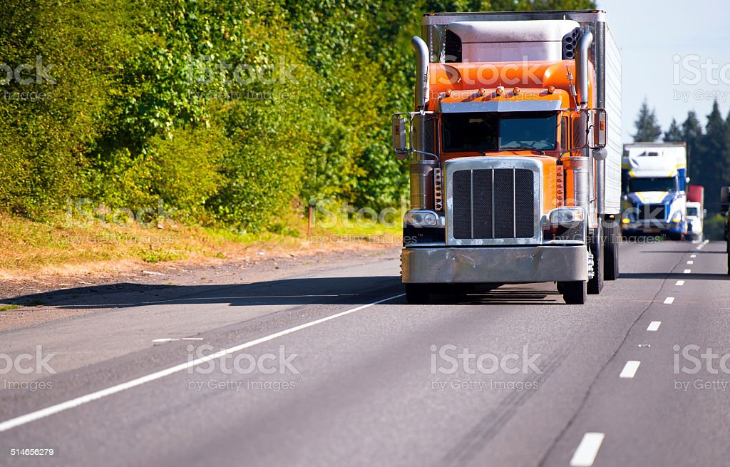Classic orange semi truck reefer trailer on high way stock photo