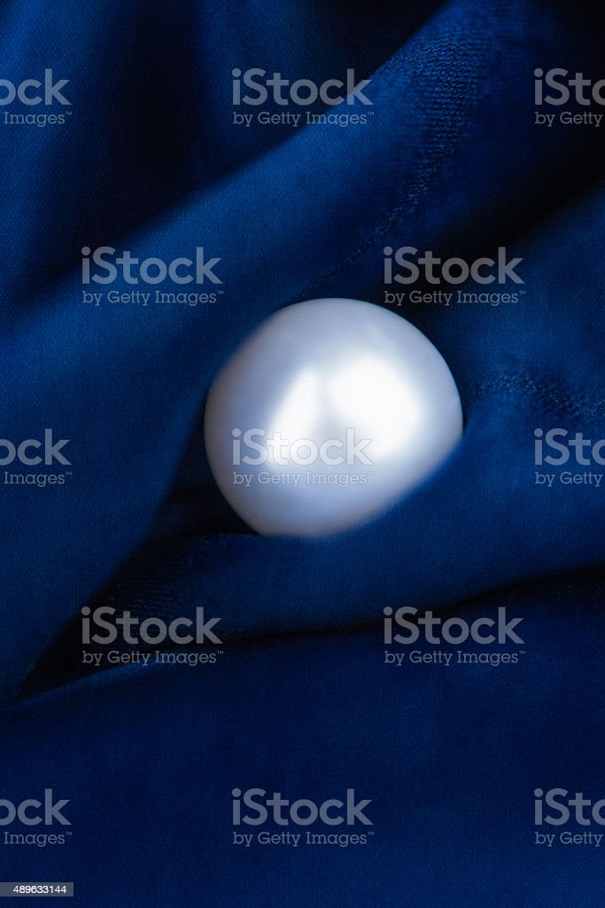 Classic pearl earring on rich sapphire blue satin background stock photo