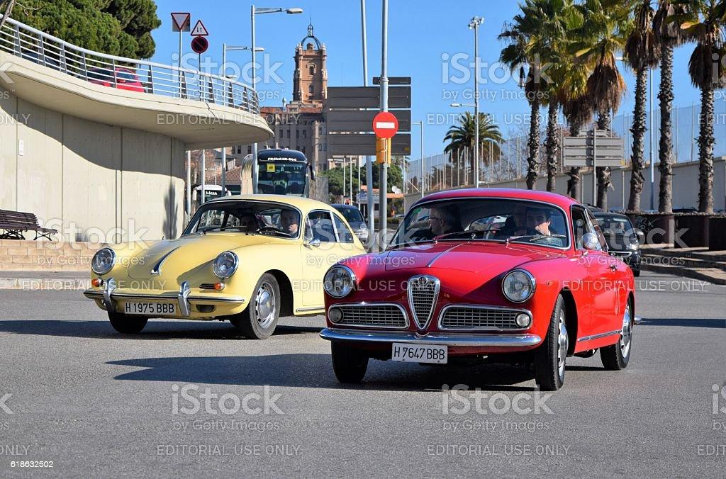 Classic Porsche and Alfa Romeo driving on the street stock photo