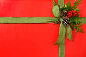 Classic red Christmas gift background with bow and natural decorations