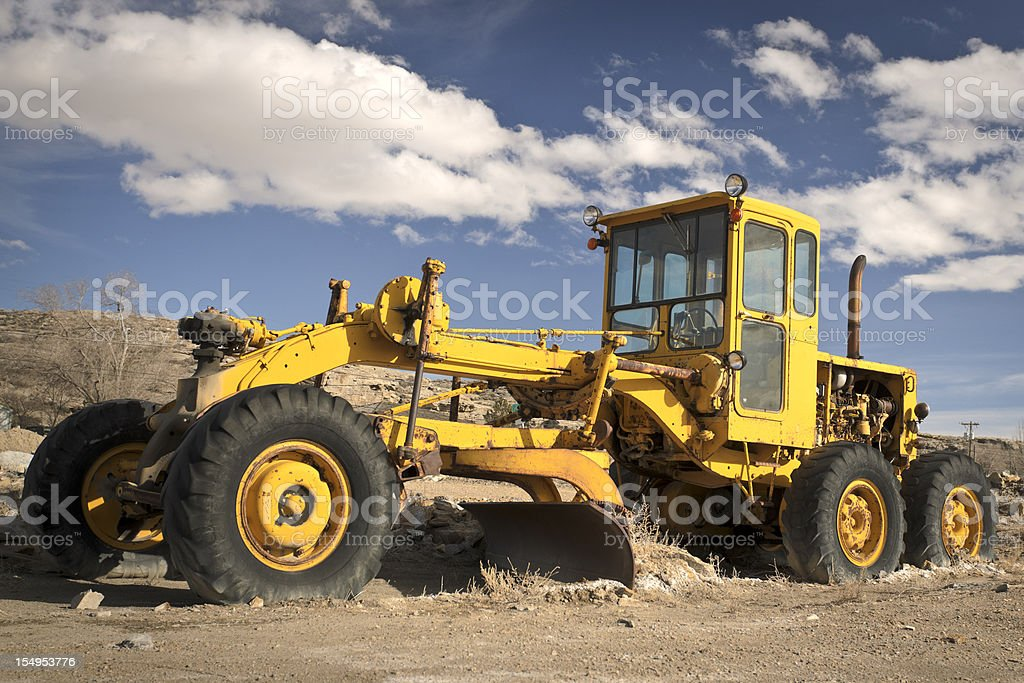 Classic Road Scraper or Grader with Perfect Cloudy Blue Sky royalty-free stock photo