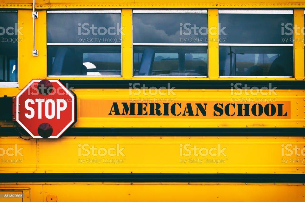 Classic yellow american school bus transporting children to the school stock photo