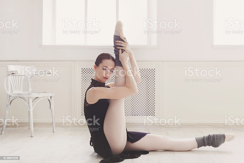 Classical Ballet dancer makes stretching in class stock photo