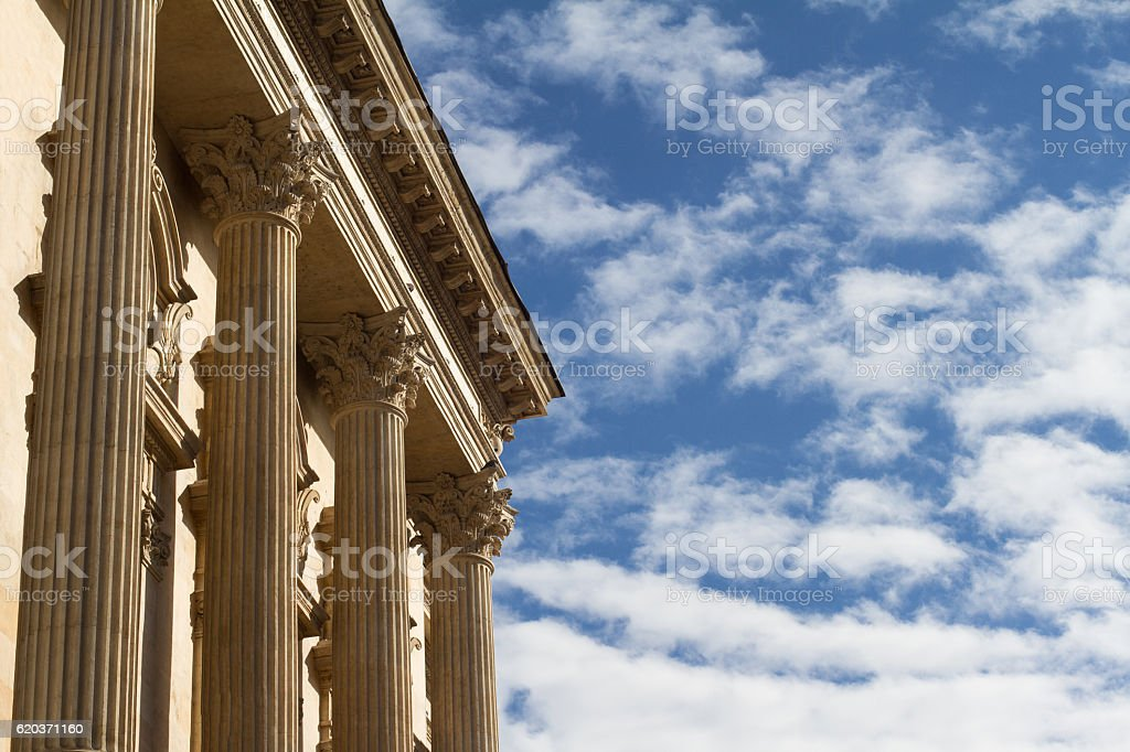Horizontal photo of classical building columns with blue sky and...