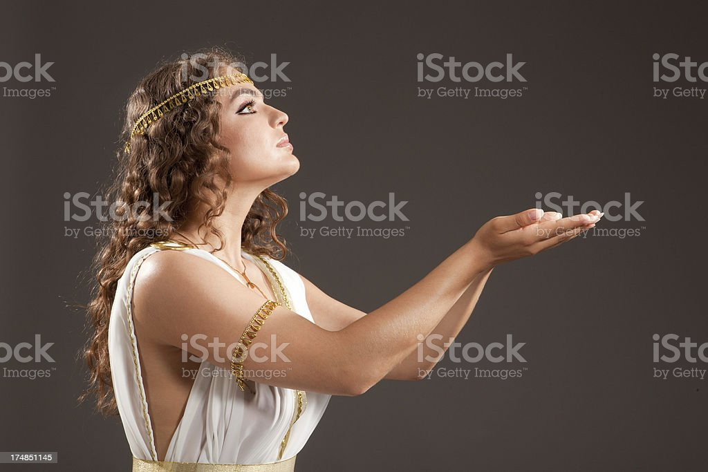 Classical Greek Goddess in Tunic Carrying Something on her Hands stock photo