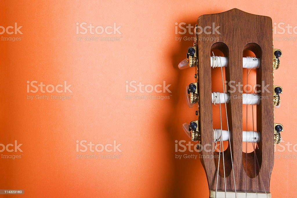 Classical guitar headstock on orange royalty-free stock photo