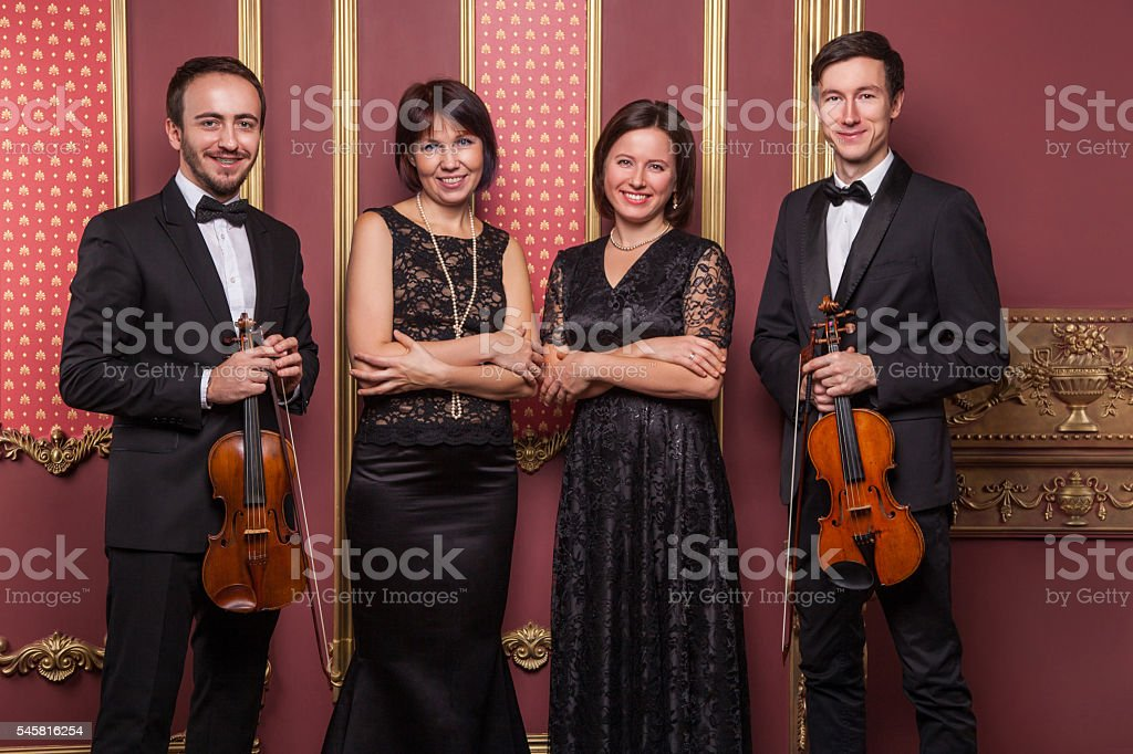 Classical music quartet posing after the concert. stock photo