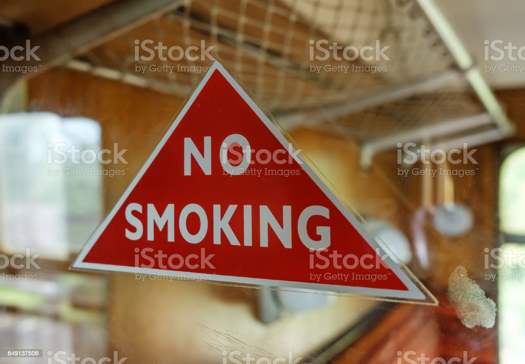 Classical No Smoking warning triangle seen attached to a glass panel at a vintage, first class train compartment. stock photo