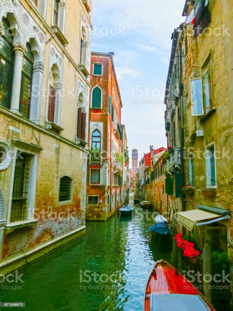 Classical picture of the venetian canals with boats across canal stock photo