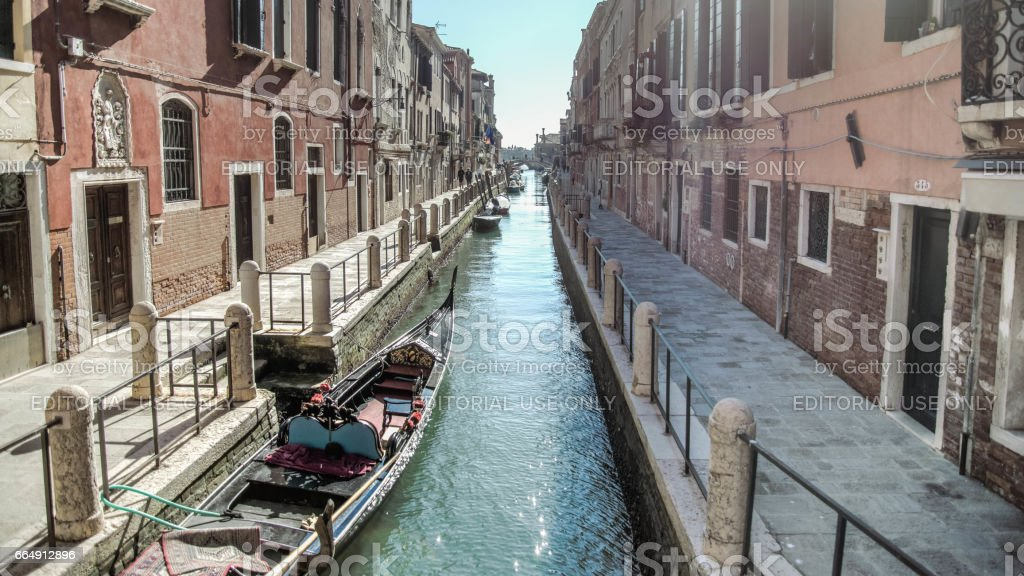 Classical picture of the Venetian canals with gondola across the canal. stock photo