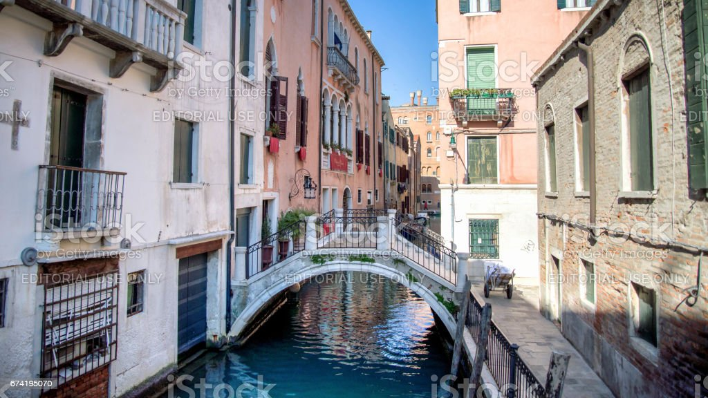 Venice, Italy - February 17, 2015:  Classical picture of the Venetian canals with gondola across the canal. stock photo