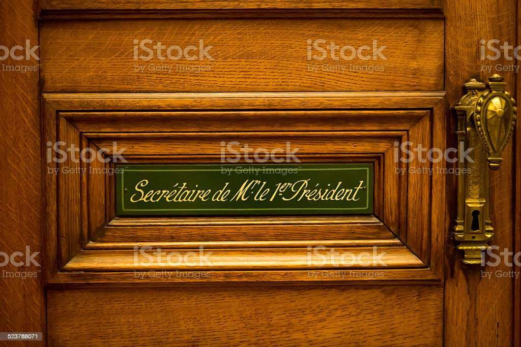 Classical style wooden door with green sign in French stock photo
