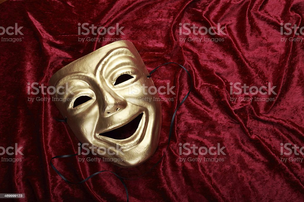 Classical theater comedy mask on a velvet curtain stock photo