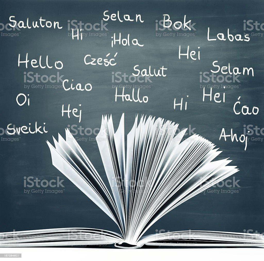 Classroom, open book, hand-written words hello, different languages, blackboard stock photo