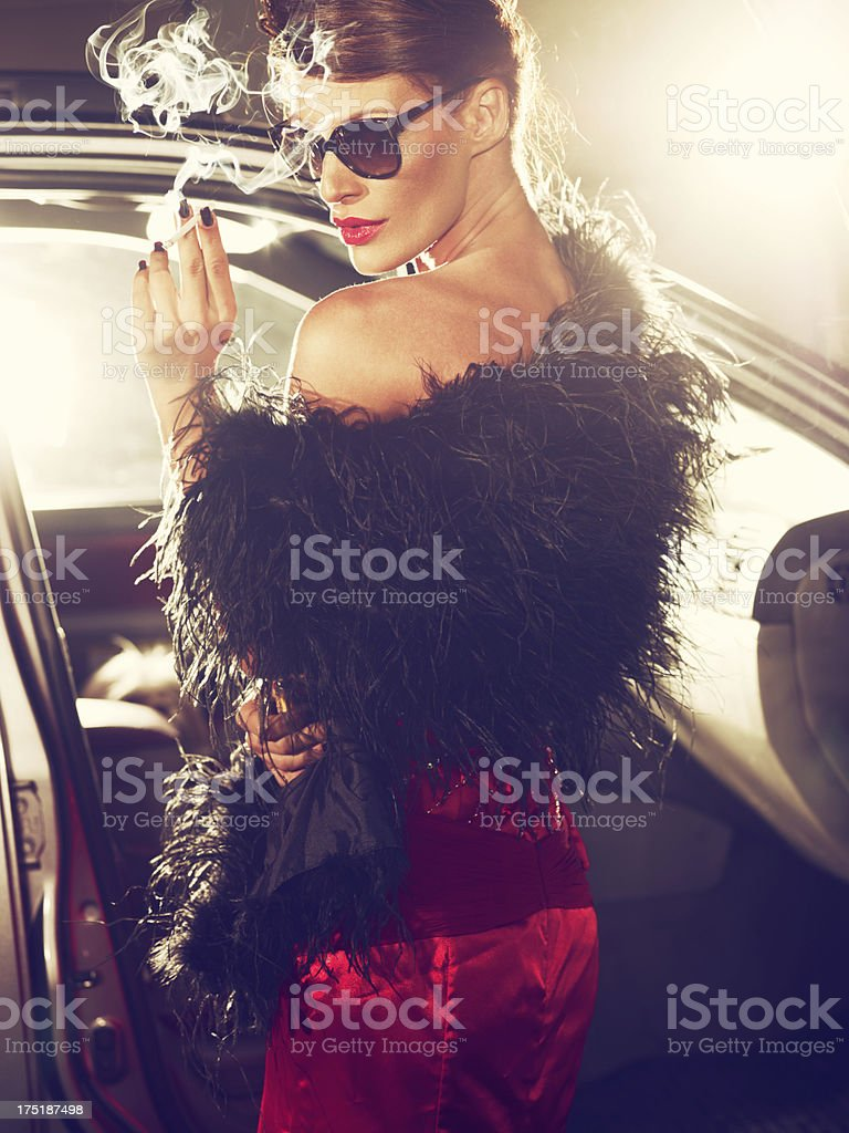 Classy woman in red evening gown with cigarette stock photo