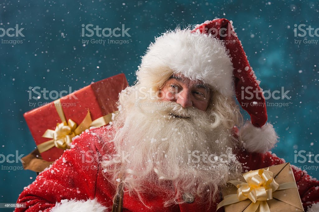Claus outdoors in snowfall carrying gifts stock photo