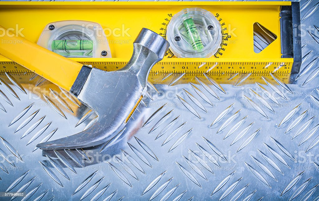 Claw hammer construction level on corrugated metal sheet stock photo