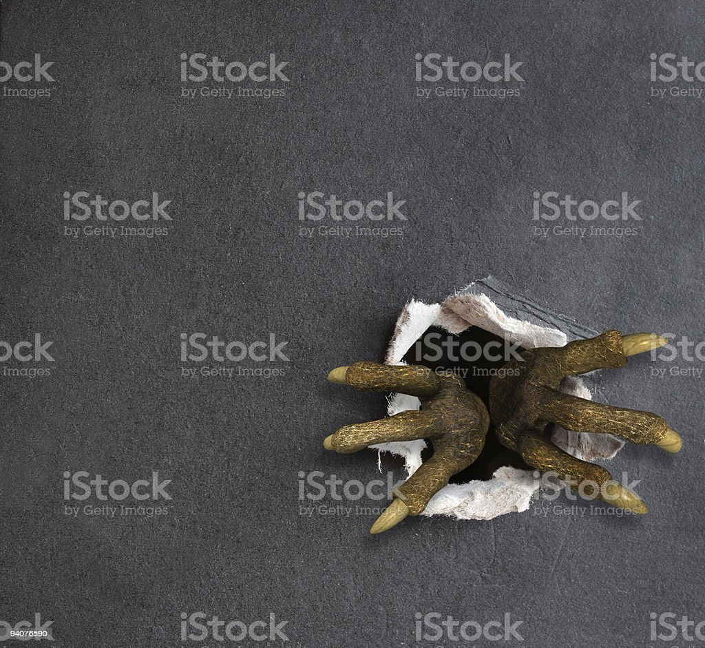 Claws penetrating through a hole in a gray wall royalty-free stock photo