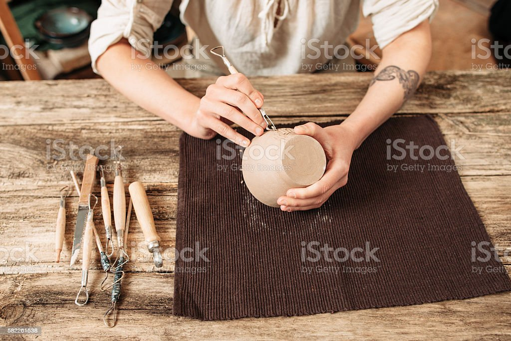 Clay bowl author decorating, pottery making stock photo
