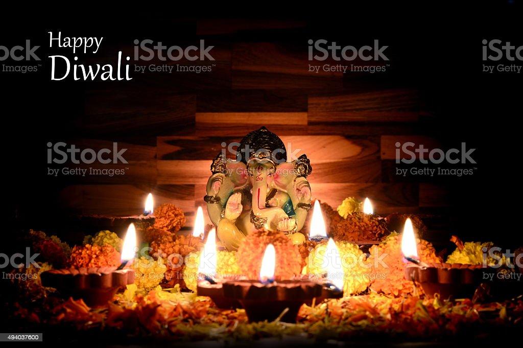 Clay diya lamps lit with Lord Ganesha during diwali celebration. stock photo