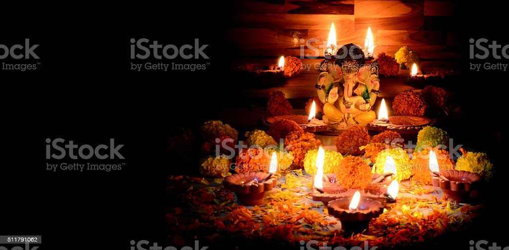 Clay diya lamps lit with Lord Ganesha during diwali celebration stock photo