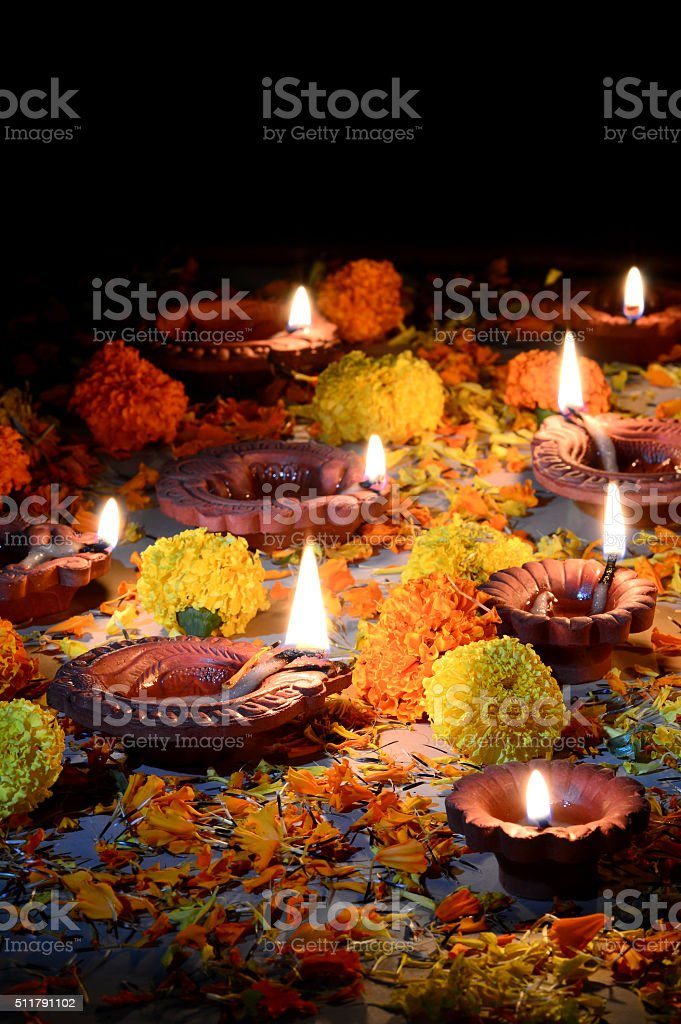 Clay diya lamps lit with Lord Ganesha during diwali celebration stock photo