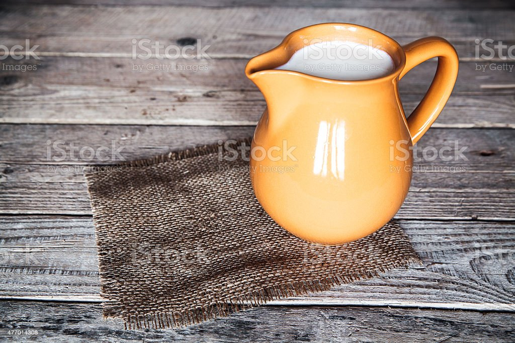 clay milk jug isolated on wooden background stock photo
