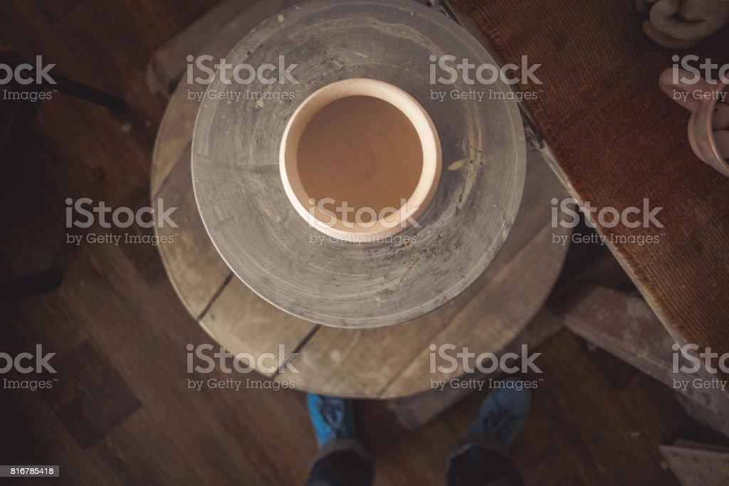 Clay pot on a potter's wheel stock photo