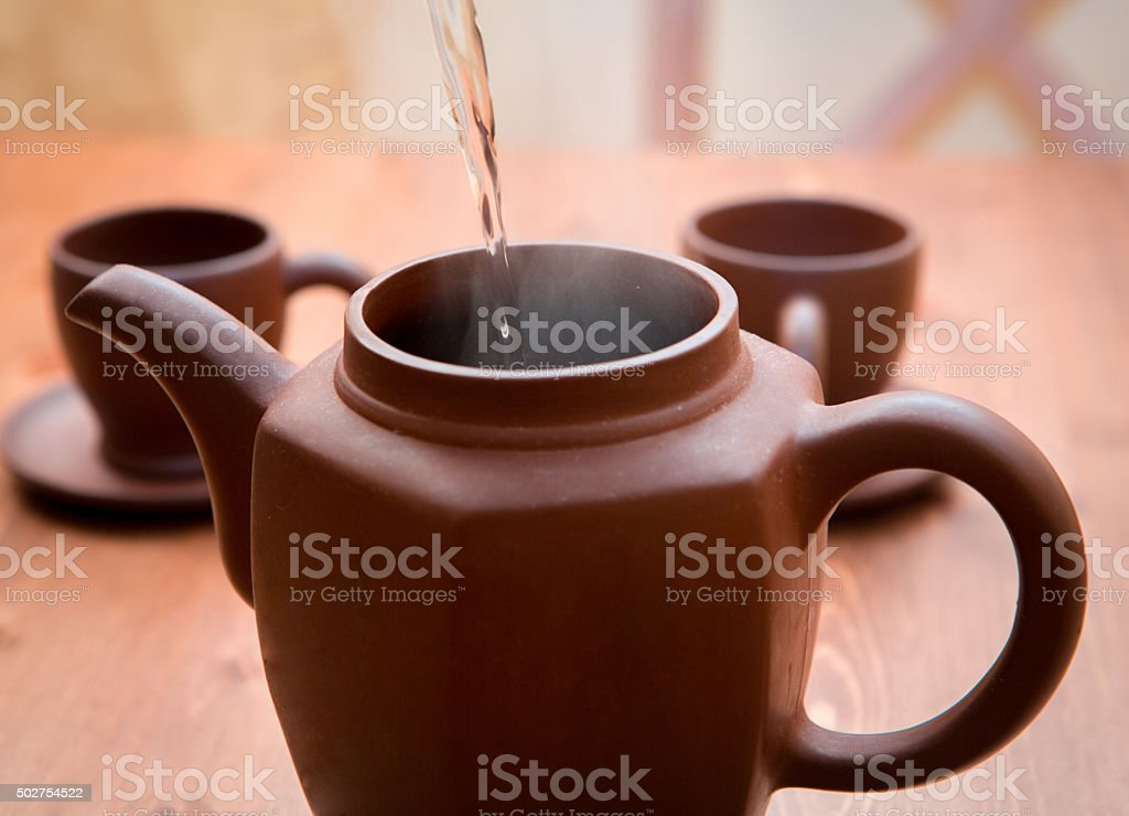 Clay teapot and cups on a wooden table stock photo