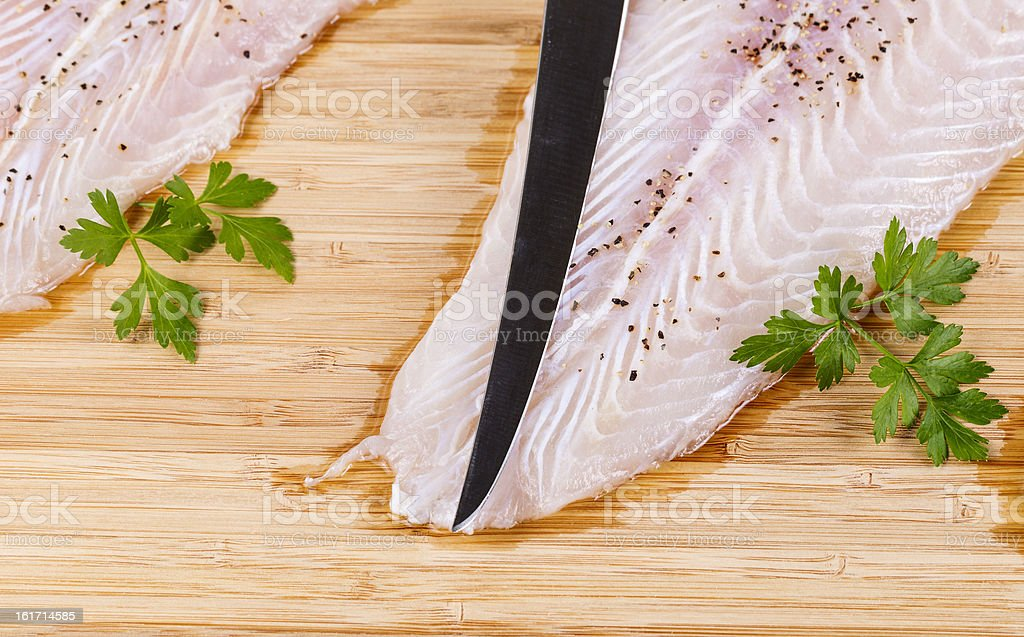 Clean and Seasoned Fish Fillets with sharp knife stock photo