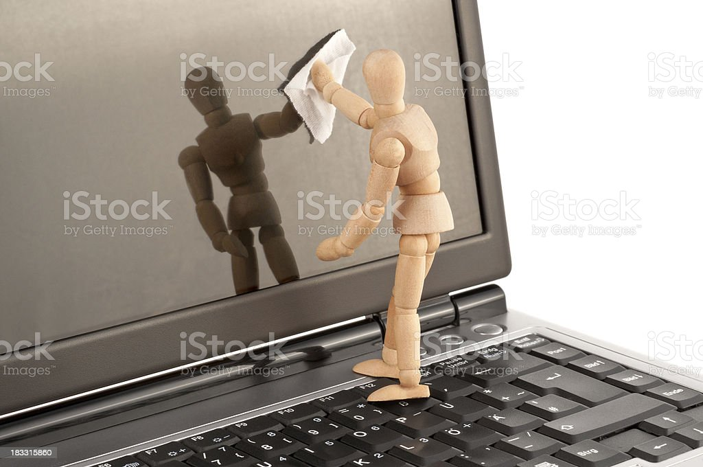 clean equipment - wooden mannequin cleaning laptop screen stock photo