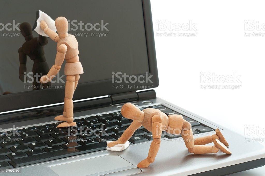 clean equipment - wooden mannequins cleaning laptop screen stock photo