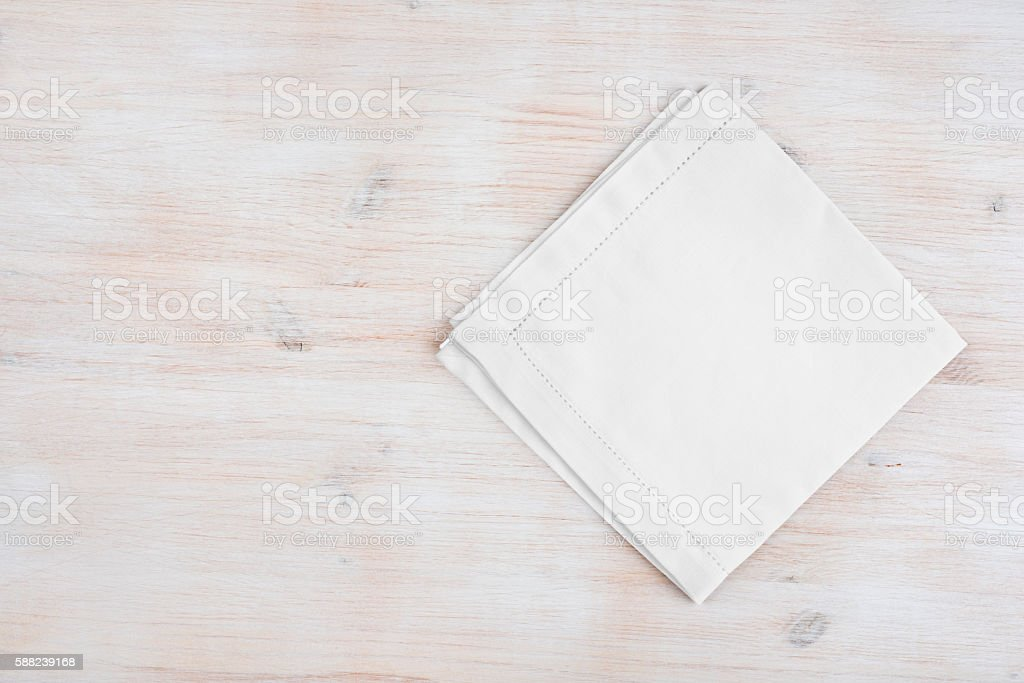 Clean folded linen napking on wooden texture background with copyspace stock photo