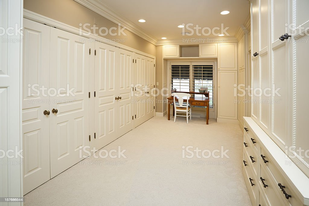 Clean, Idyllic Walk-In Closet With All White Custom Cabinetry royalty-free stock photo