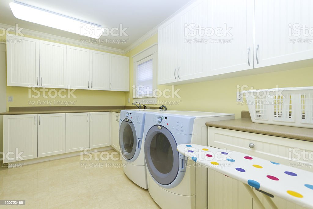Clean laundry room with machines and an ironing board stock photo